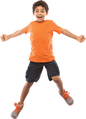 A smiling child jumping in the air, arms stretched out to the side.